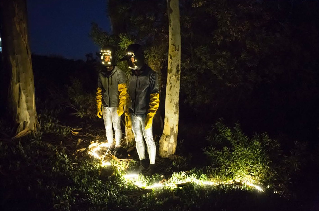 two people in masks standing in the forest